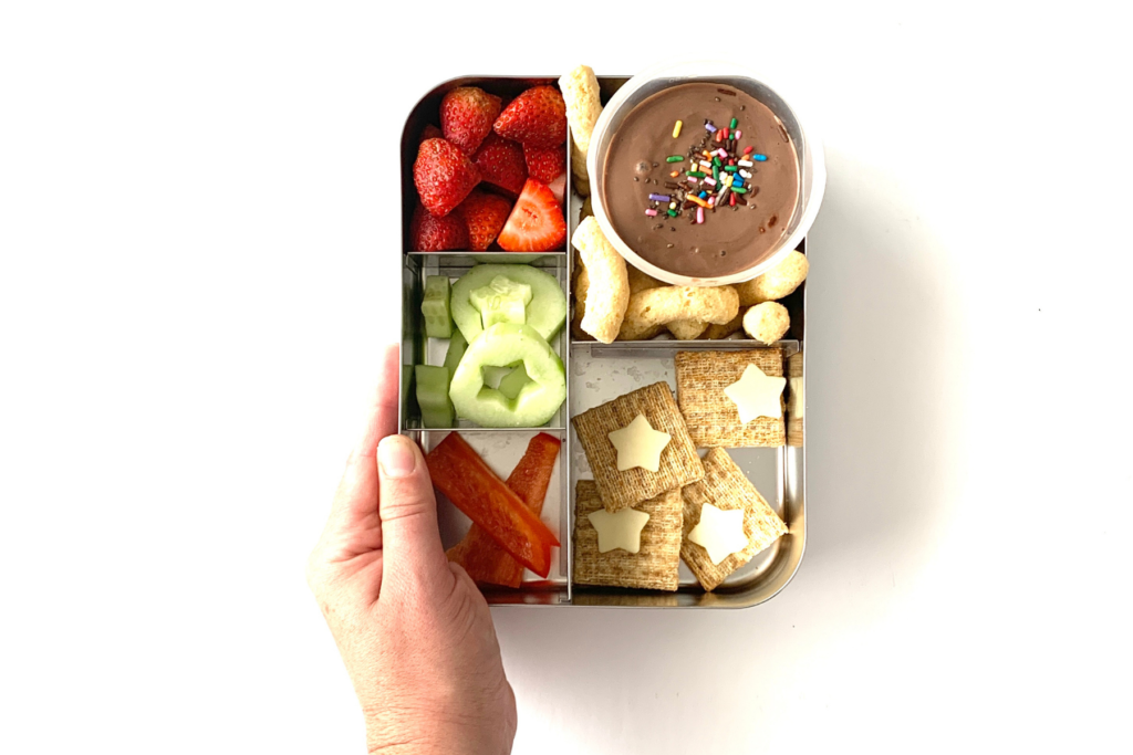 Lunch ideas for a picky eater, including, strawberries, cucumbers with star cutouts, peppers, chocolate pudding with sprinkles, chickpea puffs, crackers and star cheese.