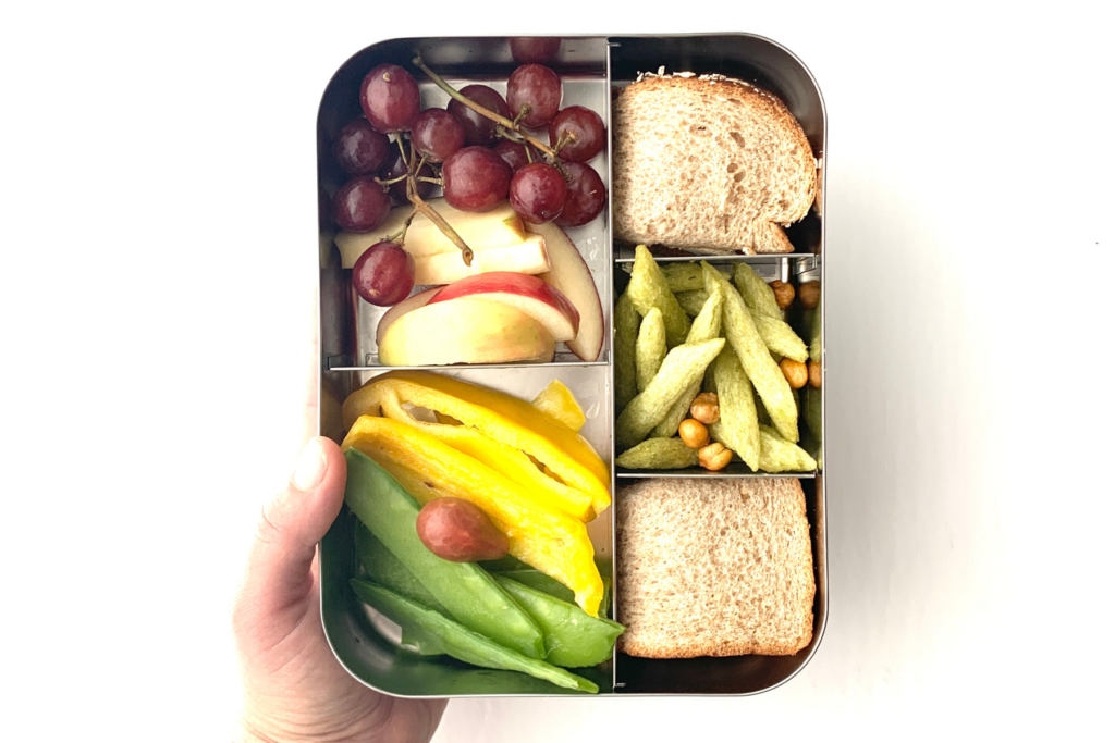 Lunch ideas for picky eater, including grapes, apples, peppers, snow peas, cherry tomato, peanut butter sandwich, pea crisps and crunchy chickpeas.