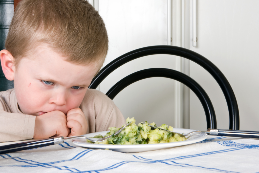 A 3 year old boy with blonde hair and blue eyes tucks his hands behind closed fists and looks sadly at the broccoli on his plate.