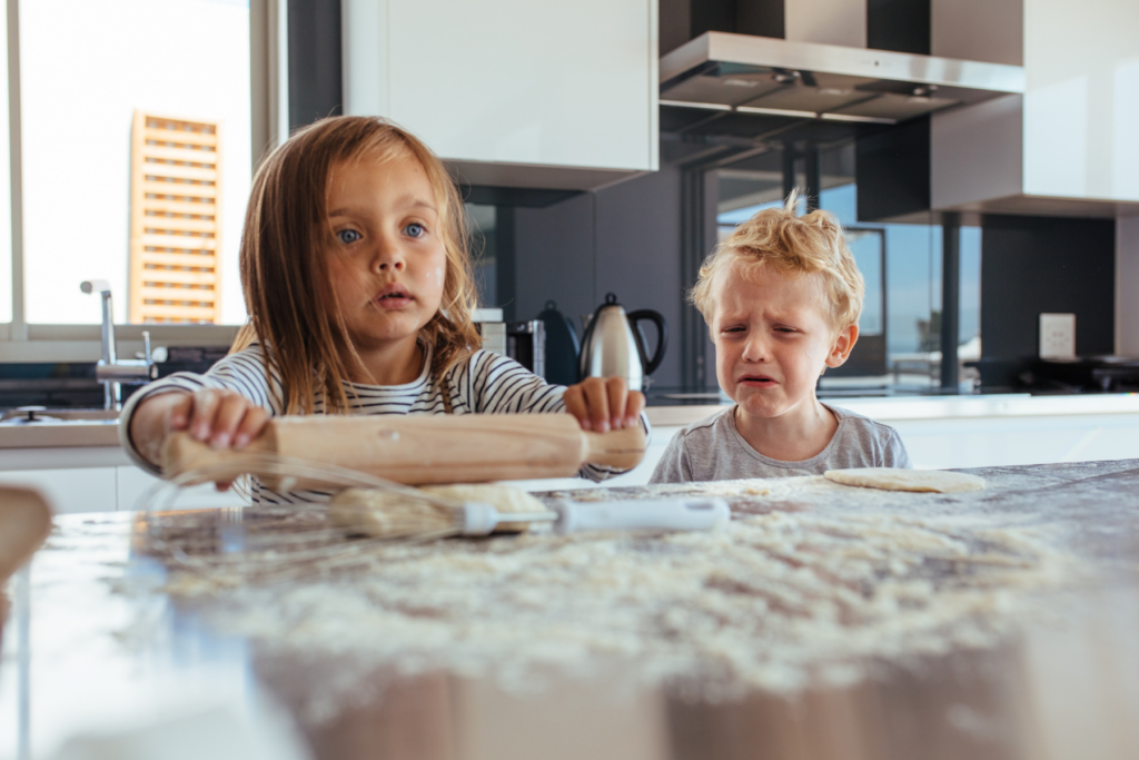 Two blonde children, about 3 years old, are standing at a kitchen counter.  A young girl, uses a rolling pin to roll dough on the floured counter.  The boy stands beside her starting to cry as he looks at the dough on the counter, possibly experiencing sensory food aversion.