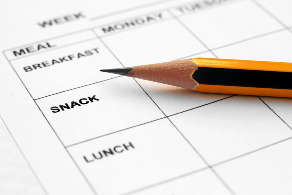 An up close photo of a meal planner with days of the week across the top and meals and snacks along the left side that can be used to make a plan to help your picky eater try new food.