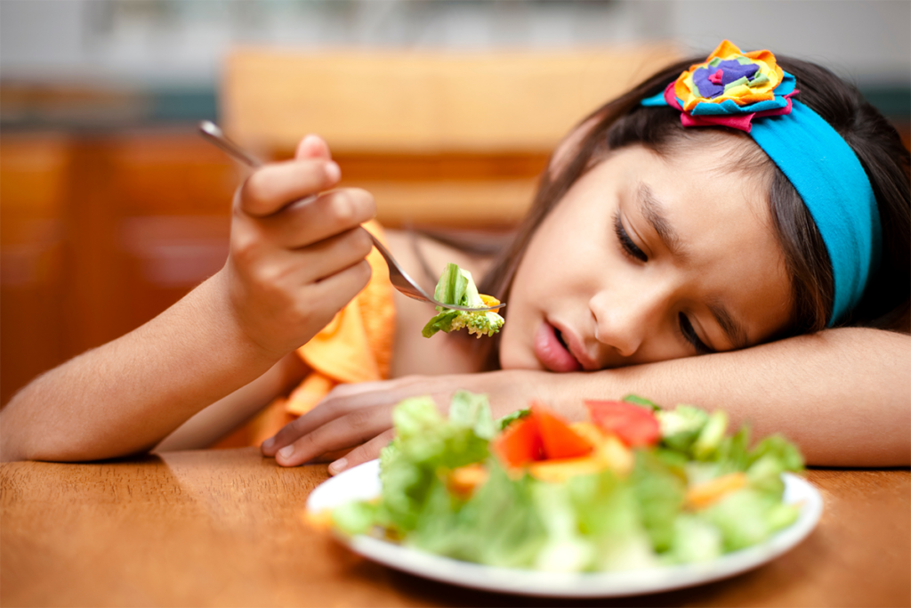 A girl about 5 years old lays her head on her arm which is laying on the table.  She holds a fork in her other hand with a bite of salad on it from the salad on her plate.  She appears to be dreading needing to take a bite.