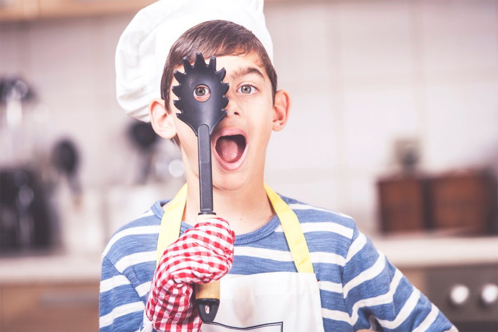 A boy with dark brown hair, wearing a chefs hat and apron, about 8 years old is holding a pasta spoon with prongs around it and a whole in the center, using a hand covered in a red and white checkered pot holder.  He holds the hold up to his eye to peer through and opens his mouth. He's ready to help his family cook, a strategy to help your picky eater try new food.