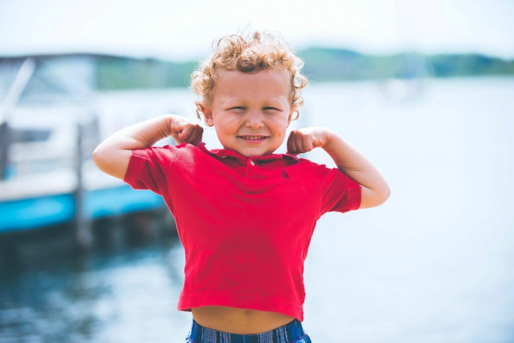 3 year old boy with blonde curly hair in a red polo shirt raises his arms to show his bicep muscles with a smile and squinted eyes