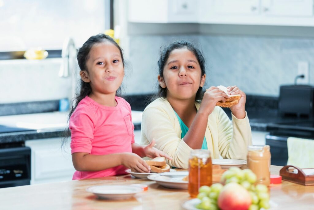 2 girls, ages 5 and 8 with long dark hair pulled half up, wearing pink and yellow respectively, are at the kitchen counter making and eating a protein food for kids, peanut butter  and honey sandwiches.  They are smiling with their mouths closed, as if they have peanut butter sticking their mouth shut.